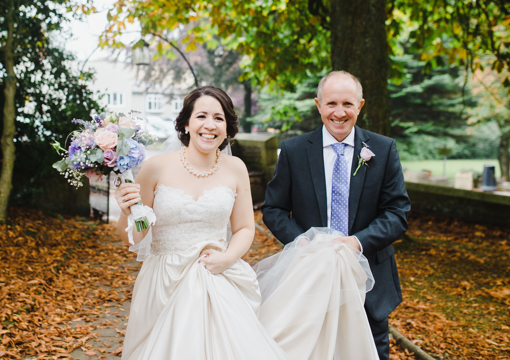 The bride and her father walking amongst the leaves at a Lancashire wedding venue- Sparth House