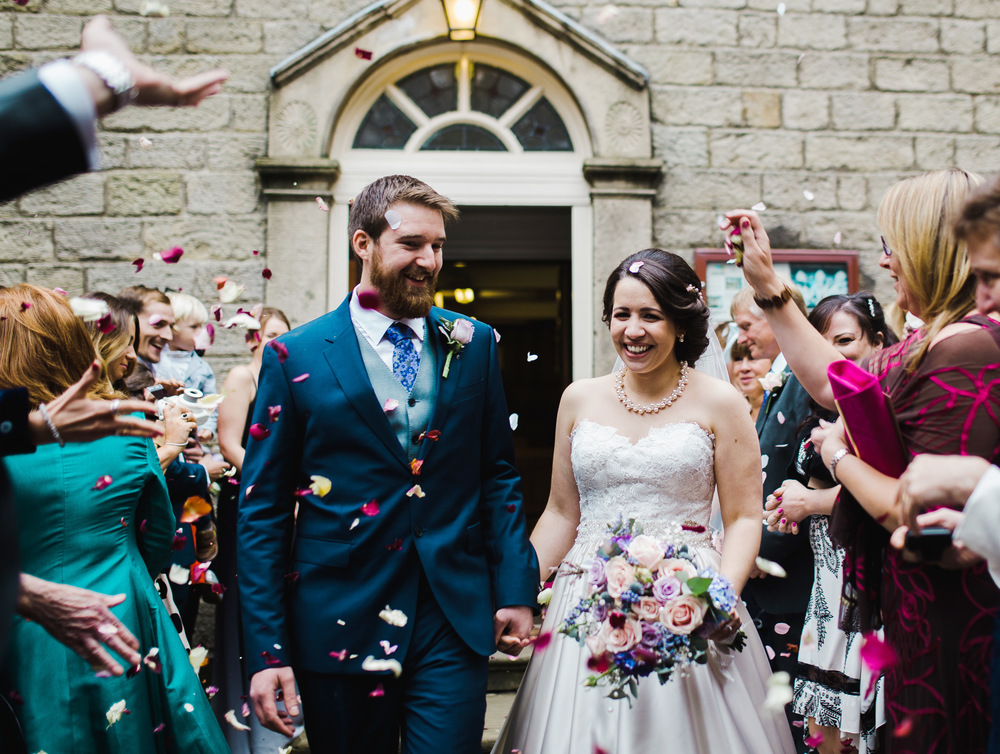 Bride and groom walk through confetti- Accrington wedding photographer