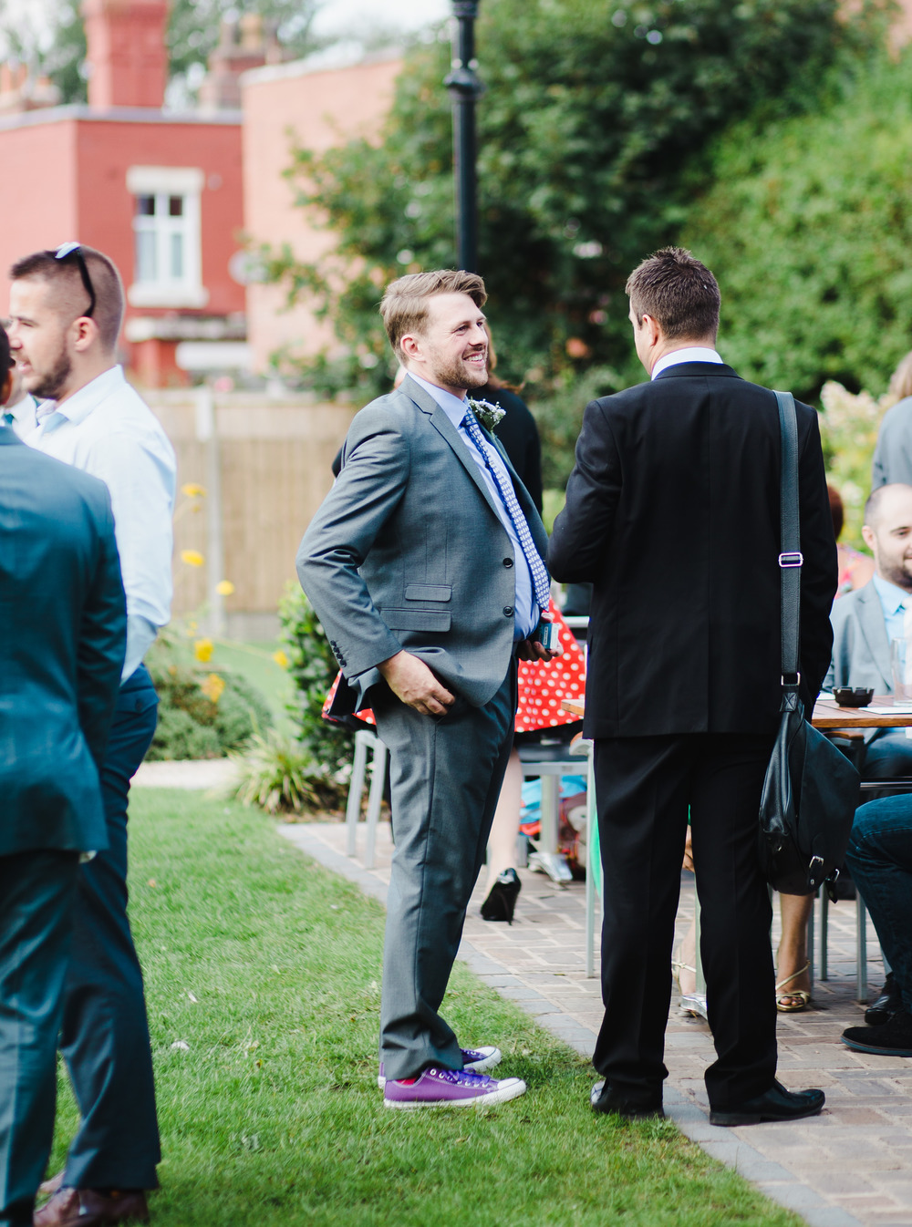 The groom with some of the wedding guests smiling, Outdoor wedding at Avenham Park
