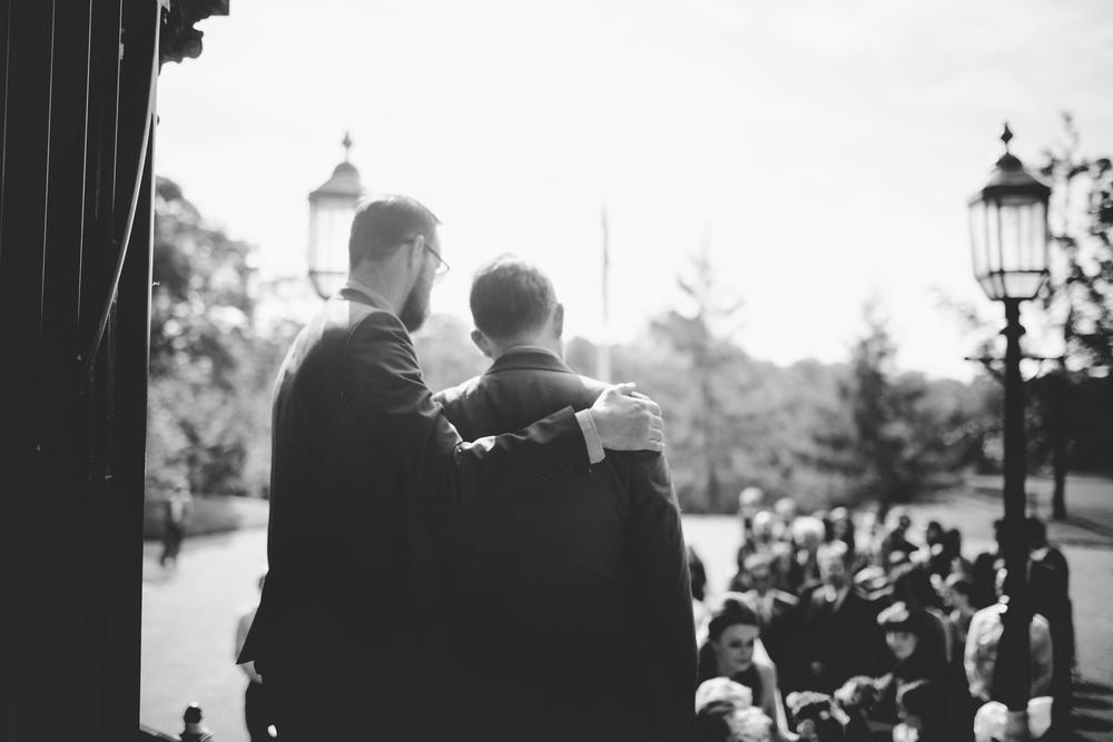 Documentary image of the batsman arm around the groom- Black and white wedding photographs