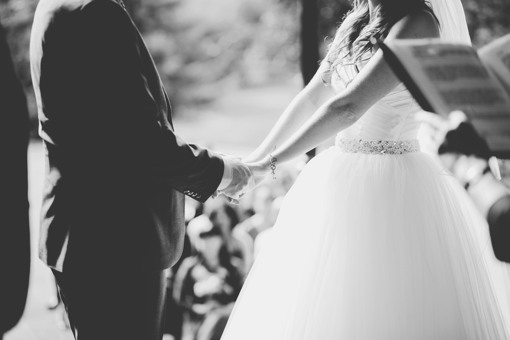 Creative image of the bride and groom holding hands, black and white photograph