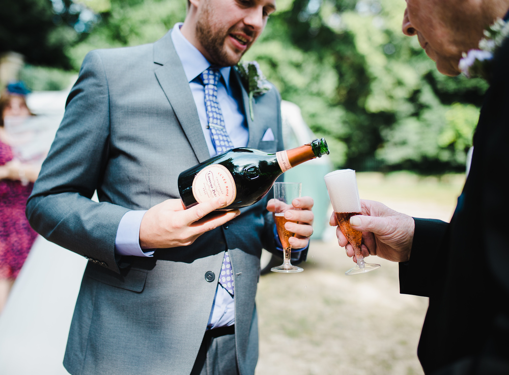 The groom pouring the champagne- Lancashire wedding photographer in preston