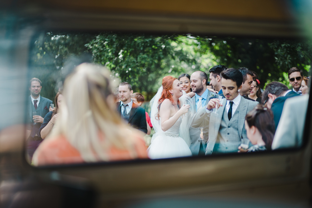 creative photograph of the bride and groom through the camper van window- Wedding photographer