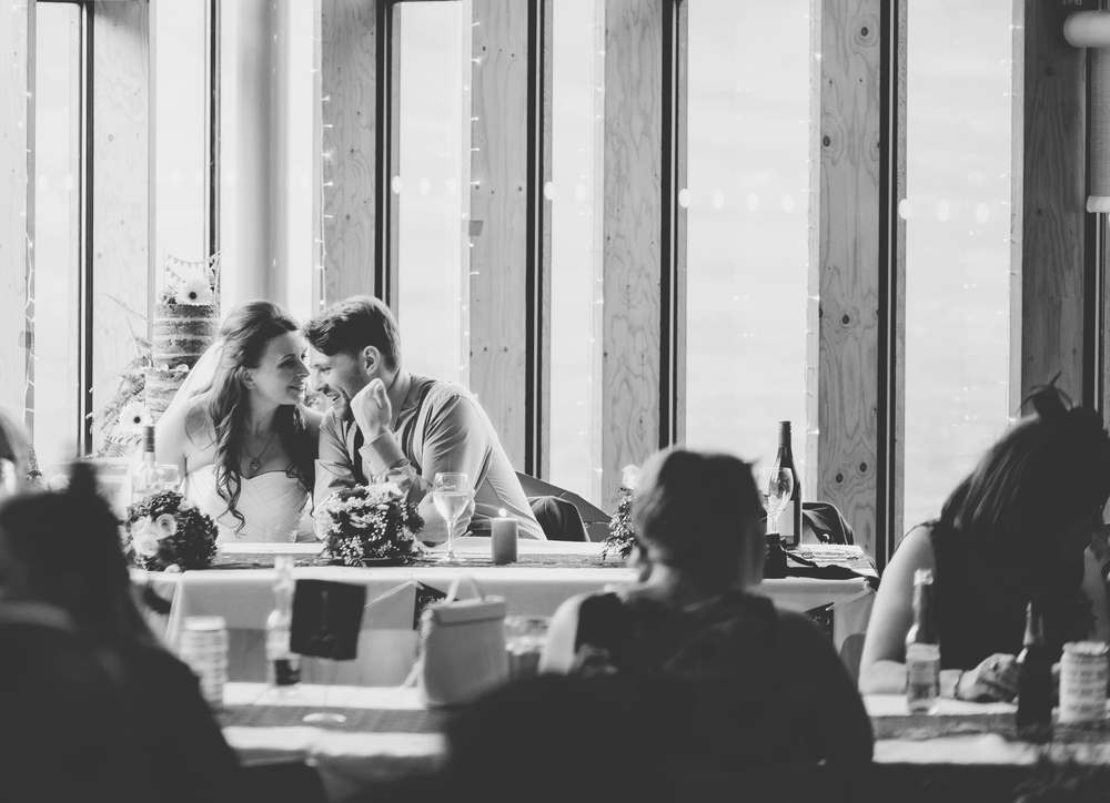 Documentary wedding photographer takes a photo of the bride and groom talking during the wedding meal- Black and white candid photograph