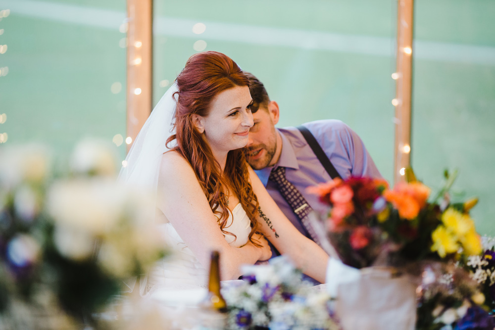 The groom whispering into the brides ear- Relaxed wedding photographer