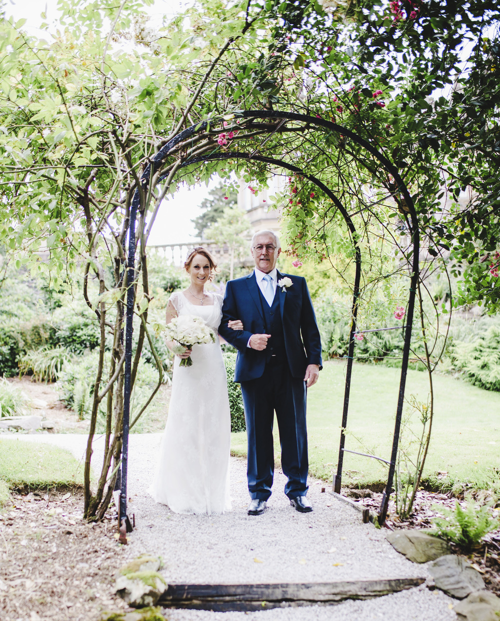 The bride and her father walking up to the wedding venue- Creative wedding photographer