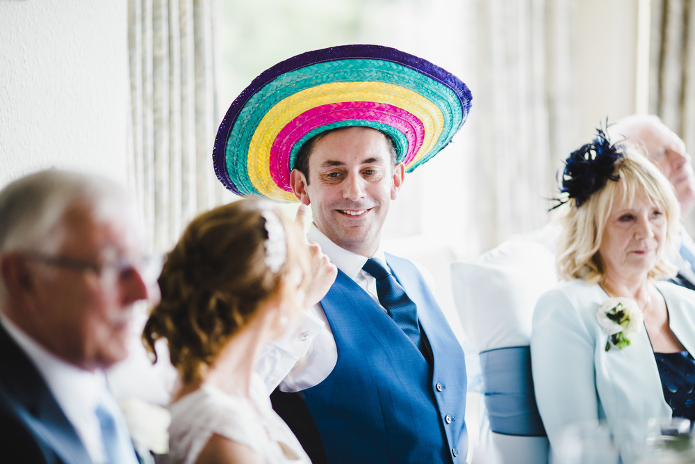 The groom wearing a multi coloured hat- Documentary wedding photographer