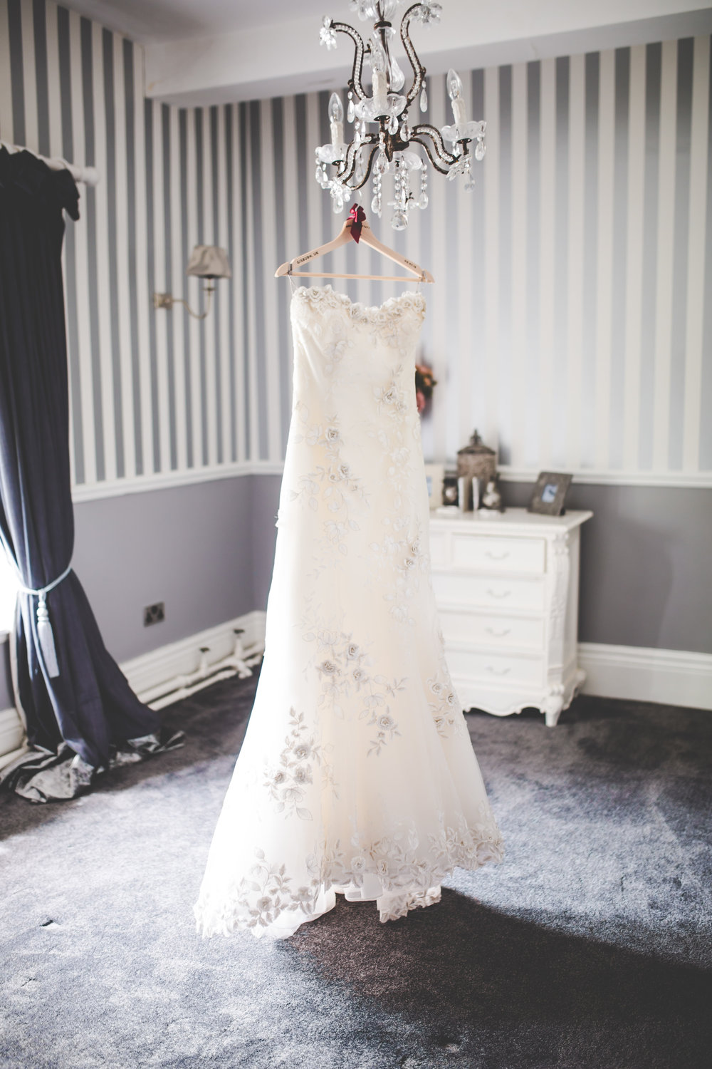 The brides dress hung up before the Lancashire wedding at Stirk House