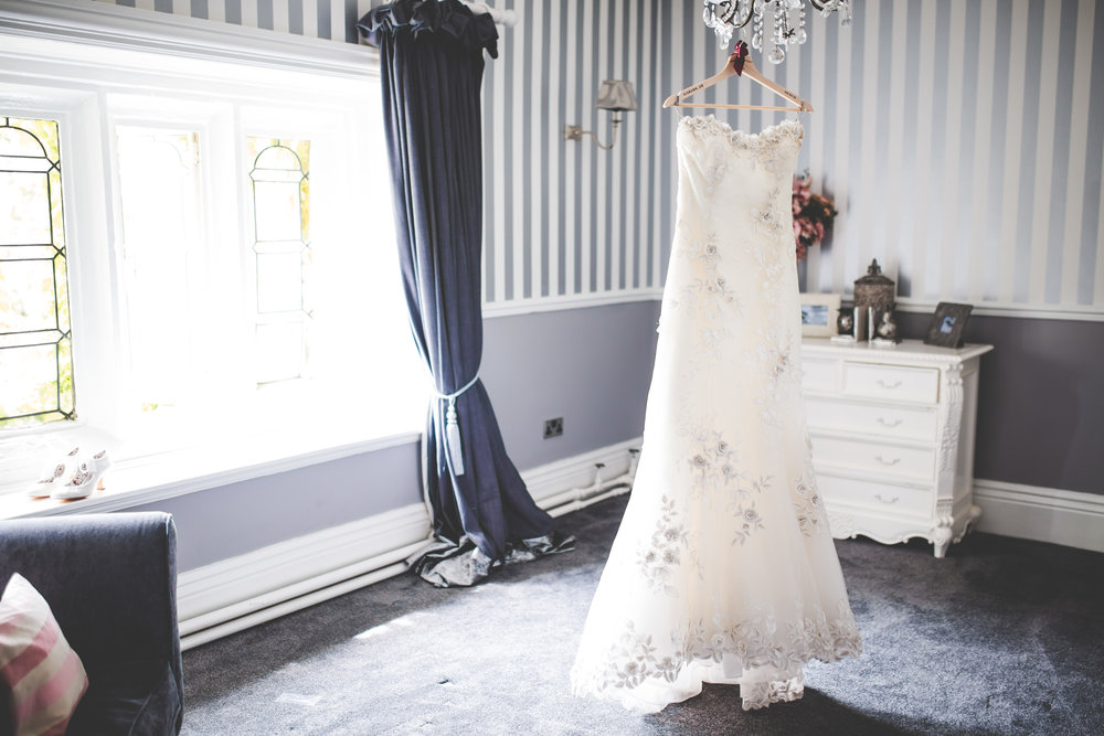 Creative photograph of the bride dress hung up on a light shade- Lancashire photography