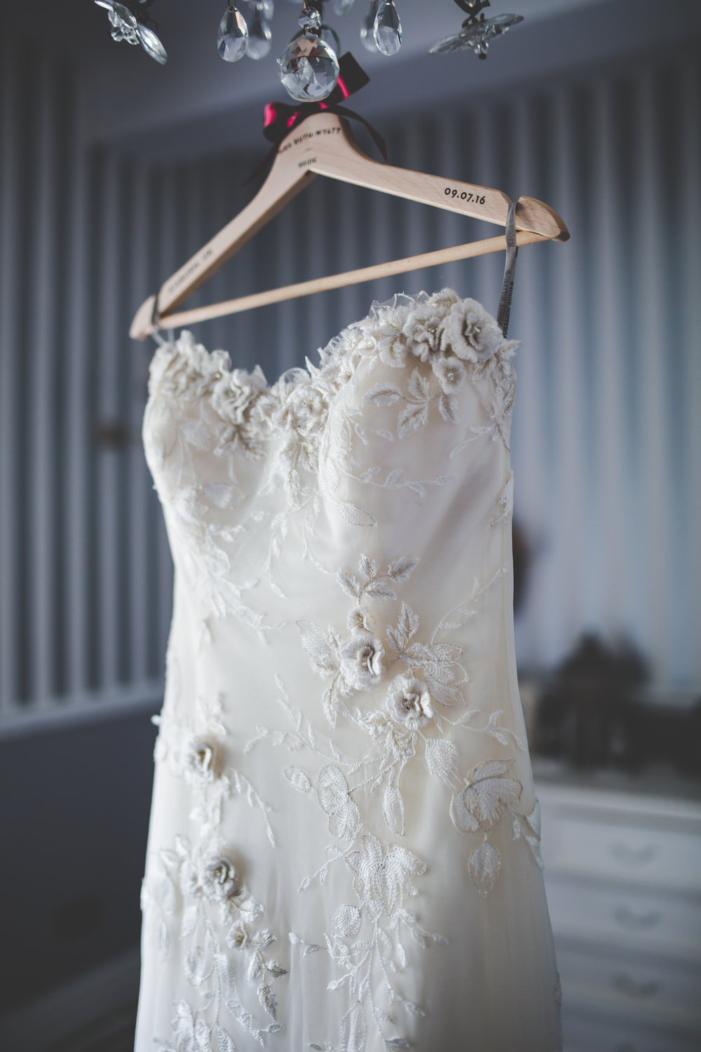 The beautiful bridal gown hung up-relaxed wedding photography