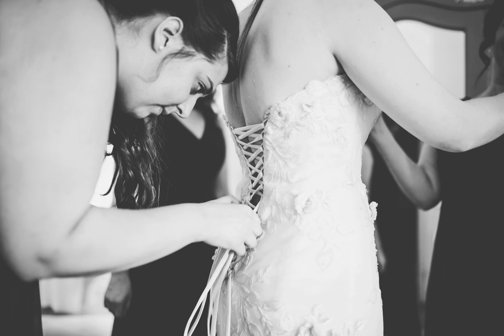 Bridesmaids helping the bride do up her dress- documentary wedding photography