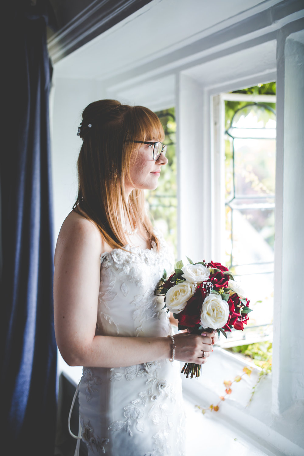 Portrait of the bride looking out of her window- creative photography