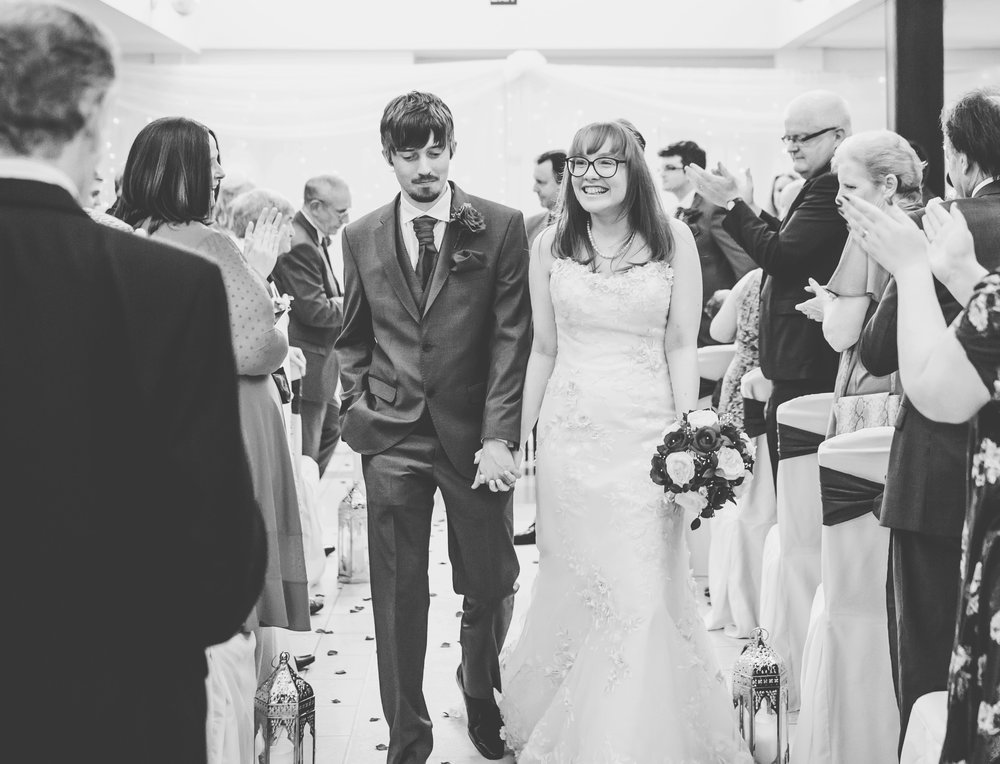 Bride and groom walking down the aisle at Stirk House, Lancashire