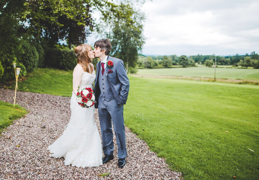 The bride and groom kissing in the fields of Stirk House Hotel- creative wedding photography