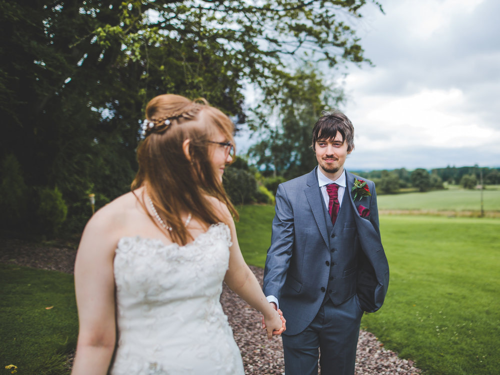 The bride and her groom walking in the wind at  Stirk House Hotel- Documentary photography