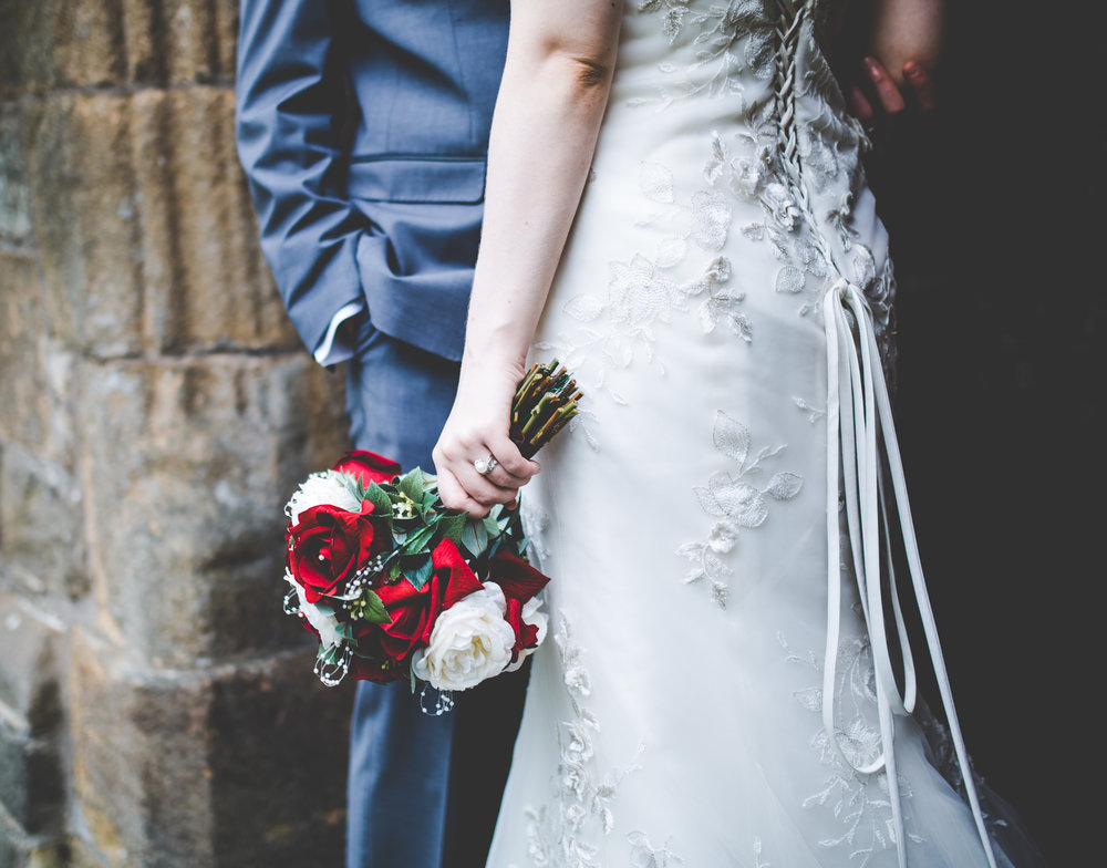 creative shot of the bride holding her wedding bouquet and the groom