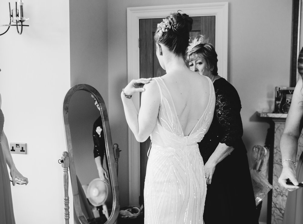 The bride in the wedding gown stood infront of the mirror- Documentary photography