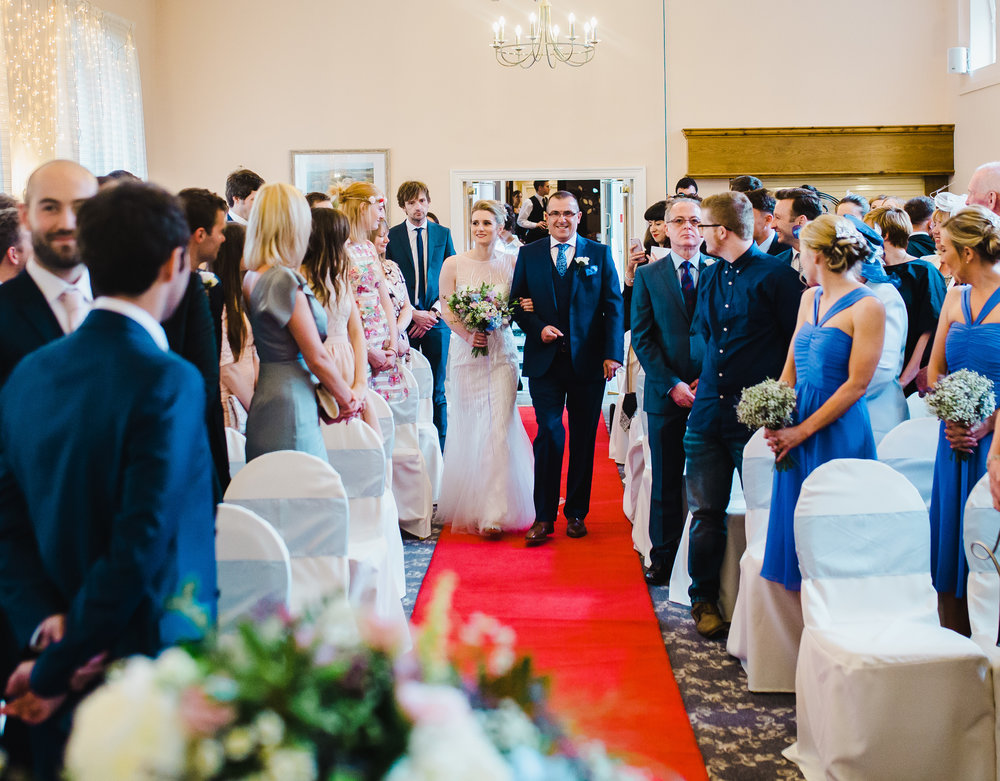 The bride and father walking down the red carpeted aisle. - Modern wedding photography