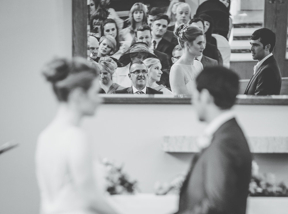 Documentary photograph of the bride and groom holding hands at the alter.