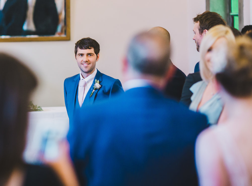 Far away photograph of the groom smiling as the bride walks down the aisle with her father- Relaxed wedding photography