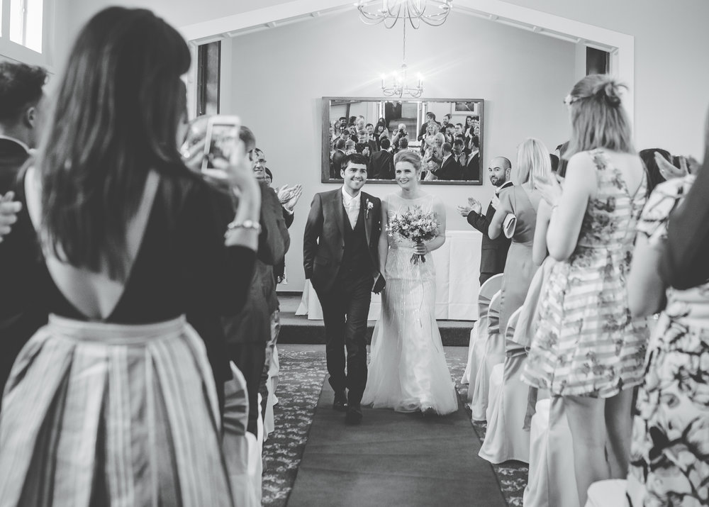 The bride and groom walking down the aisle, black and white wedding photography