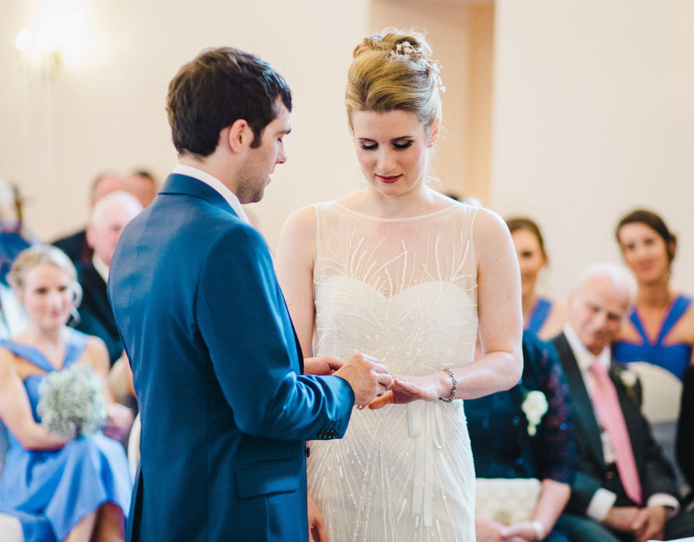 The groom putting the ring on his bride- Documentary wedding photography