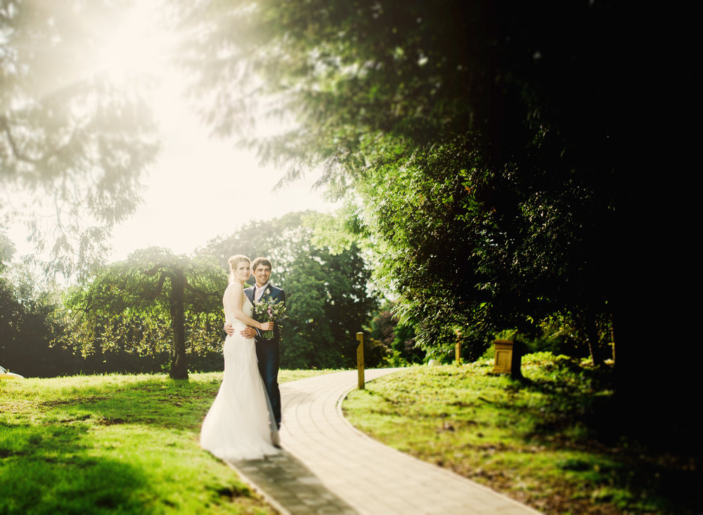 Creative wedding photograph of the bride and groom featuring the sun setting- Villa at Levens