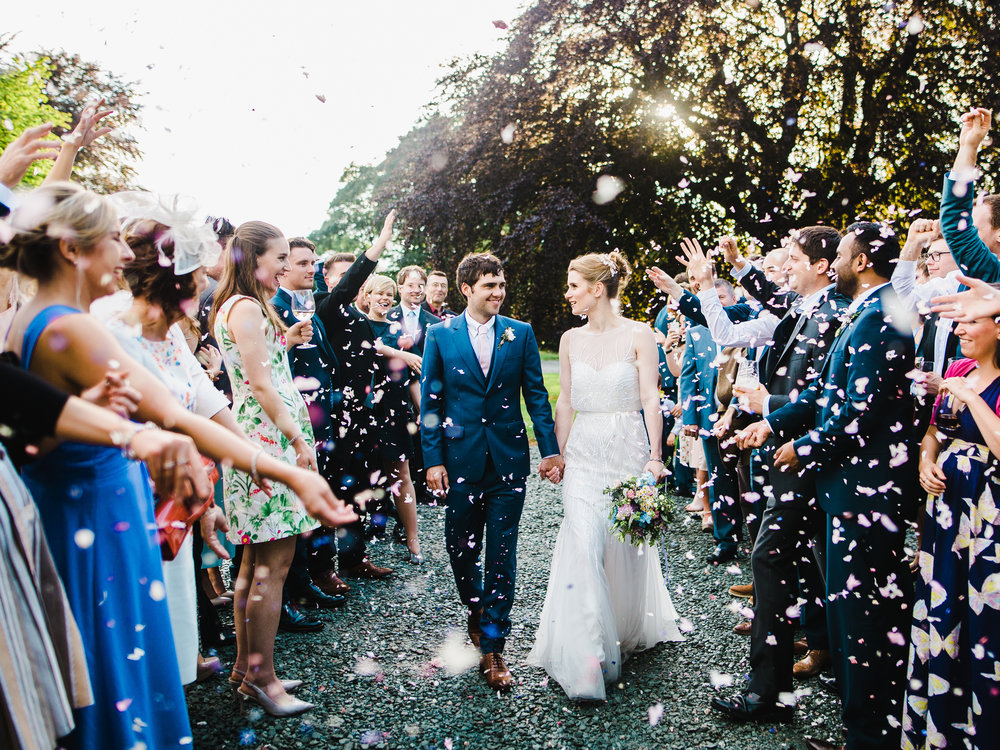 The groom and bride walking through confetti- Lake district wedding