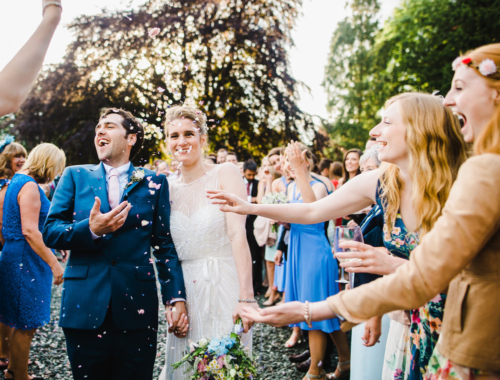 The bride and groom as confetti gets thrown in the air- Villa at Levens for a modern wedding