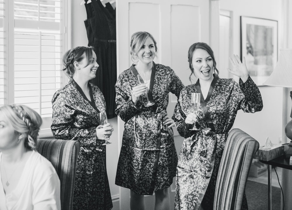 Documentary photograph of the bridesmaids holding champagne while getting ready.