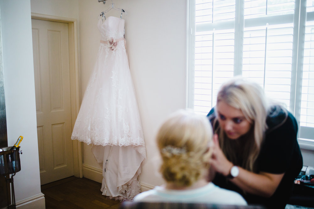 The bride getting her makeup done, featuring the brides beautiful wedding gown- Lancashire wedding photographer