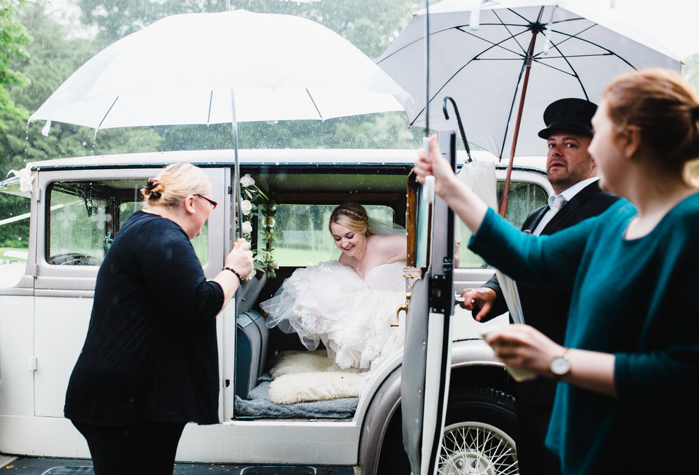 The bride getting out of her car in the rain, umbrella at the ready. Creative photography.