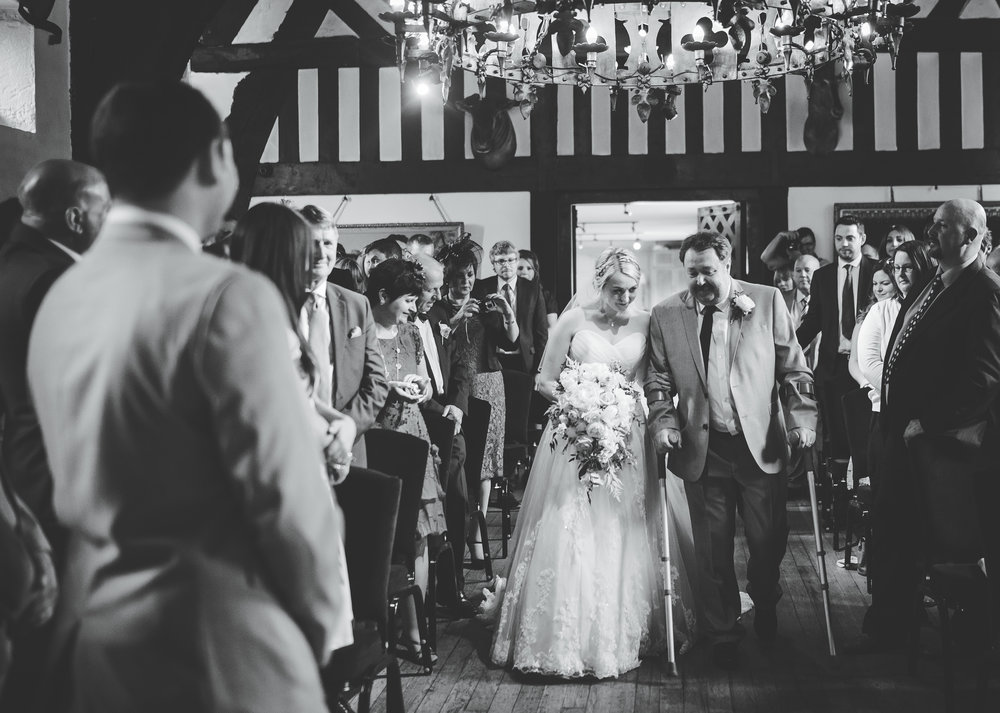 Black and white documentary photo of the bride and her father walking down the aisle.