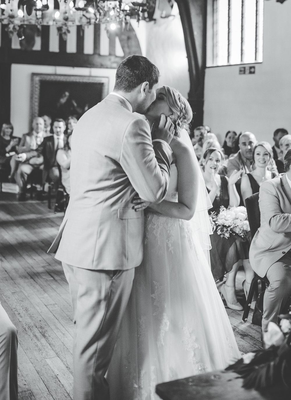 Black and white photograph of the bride and groom kissing.- Documentary photographer