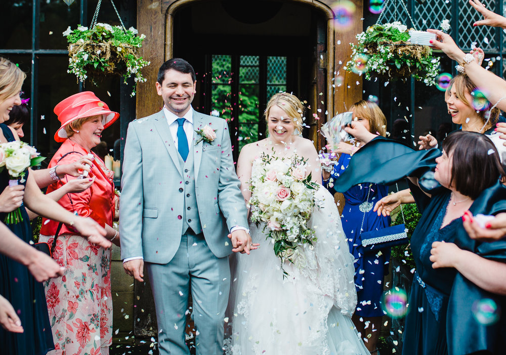 The bride and groom walking out into confetti filled air- Preston wedding photographer