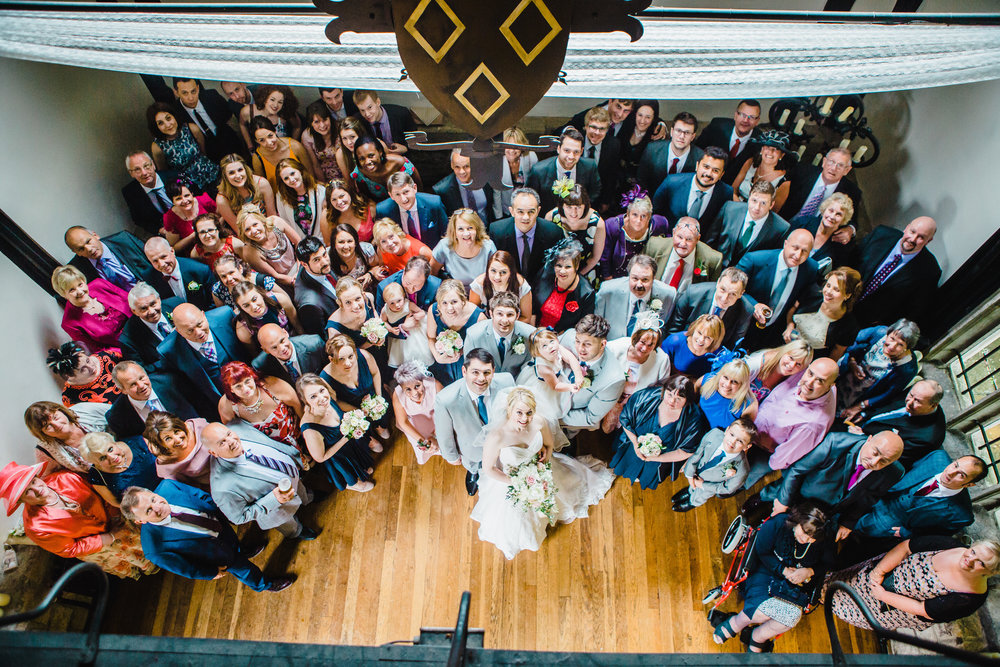 Bird's-eye view of the bride and groom surrounded by their wedding guests.