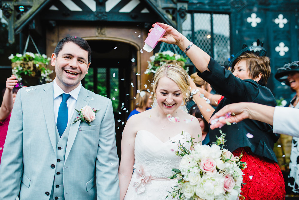 Smiles from the new Mr and Mrs walking through confetti outside of Samlesbury Hall- Lancashire wedding photography