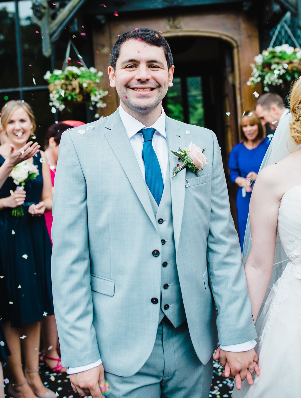 Big smile from the groom as he holds his brides hand- Documentary photography