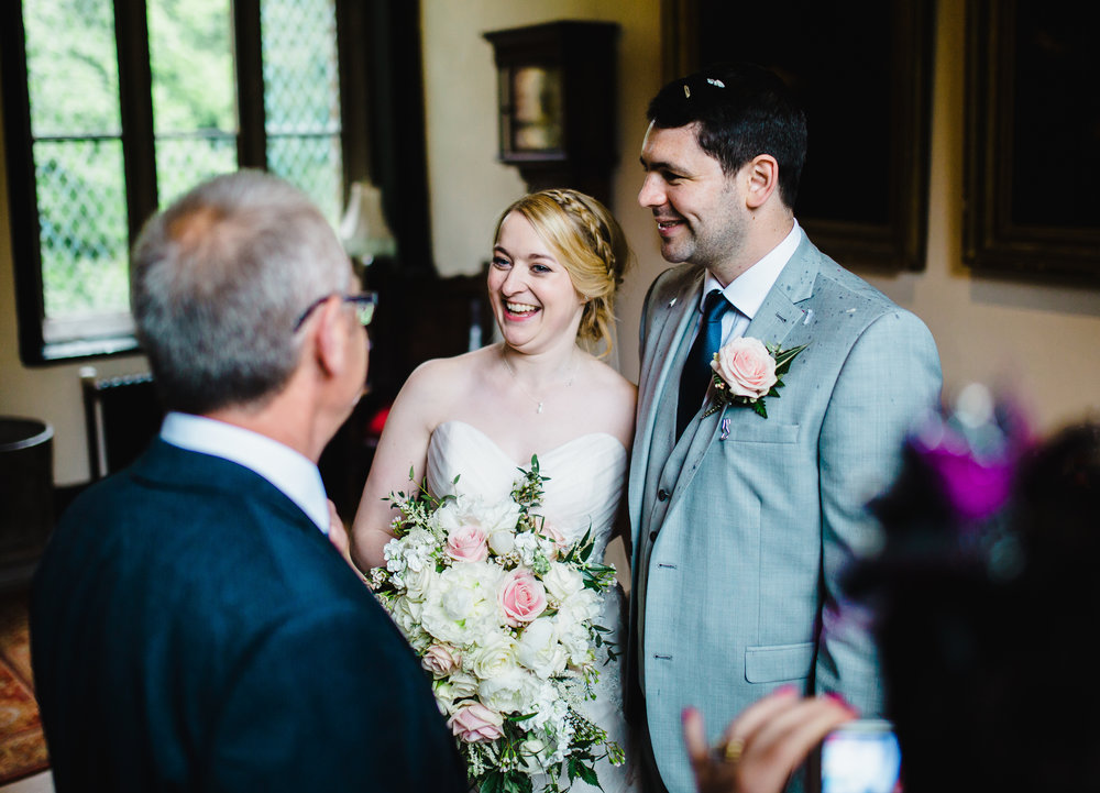 The bride and groom with a few of their wedding guest inside of Samlesbury Hall, preston Lancashire