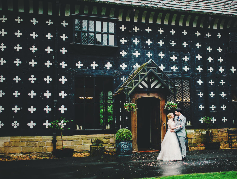 Creative photograph of the bride and groom stood outside of Samlesbury Hall- Wedding photographer, relaxed