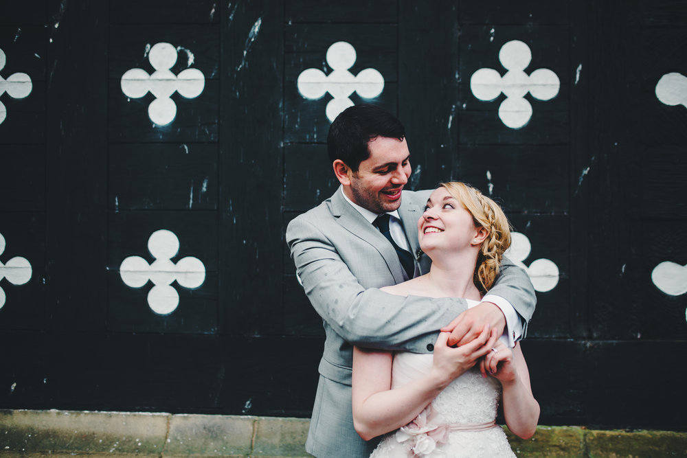 The bride and groom smiling at one another outside their wedding venue, Samlesbury Hall- Preston wedding photography