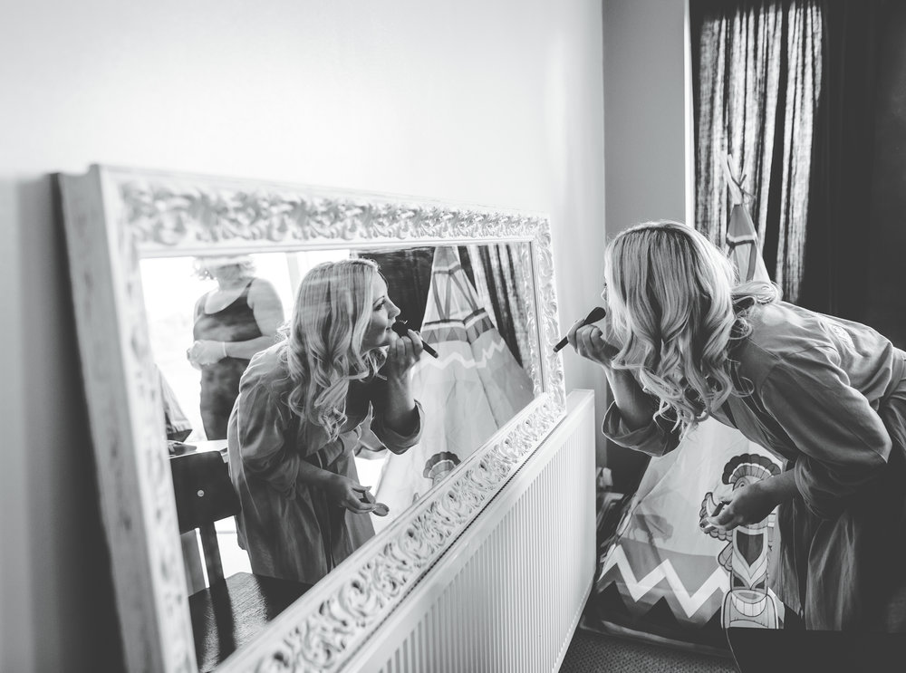 The bride putting on makeup for the lancashire wedding