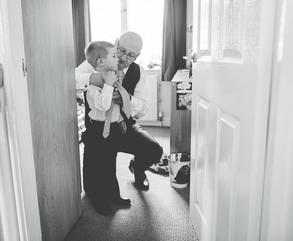 One of the little ones being taught how to tie a tie, Documentary wedding photography