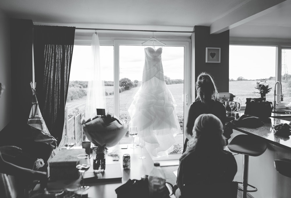 Documentary photograph of the bride getting her hair done featuring the bridal gown