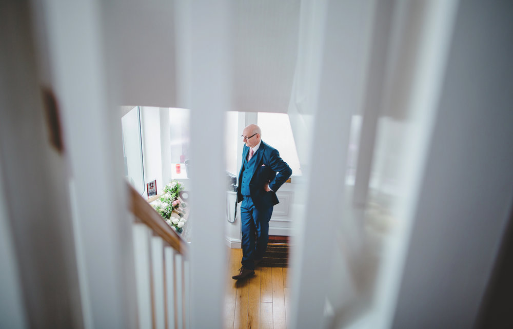 Creative wedding photography of the father of the bride looking through the stair railings.