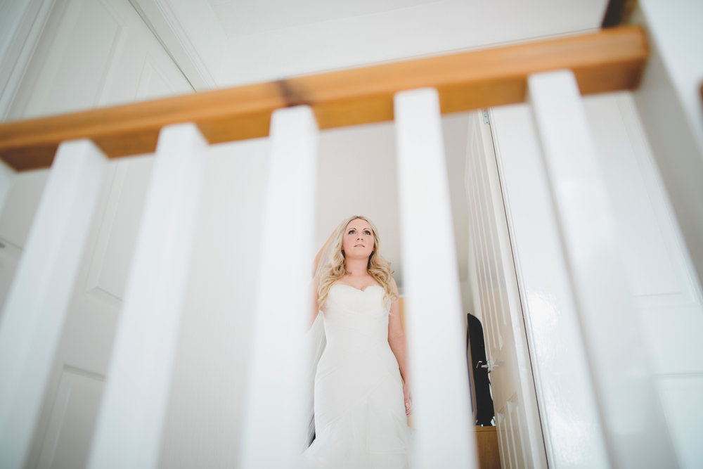 The bride walking down the stairs in her wedding dress- Modern wedding photographer, lancashire