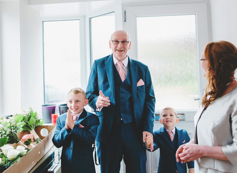 The father of the bride as he watches the bride walk through the door in her dress- Documentary wedding photography