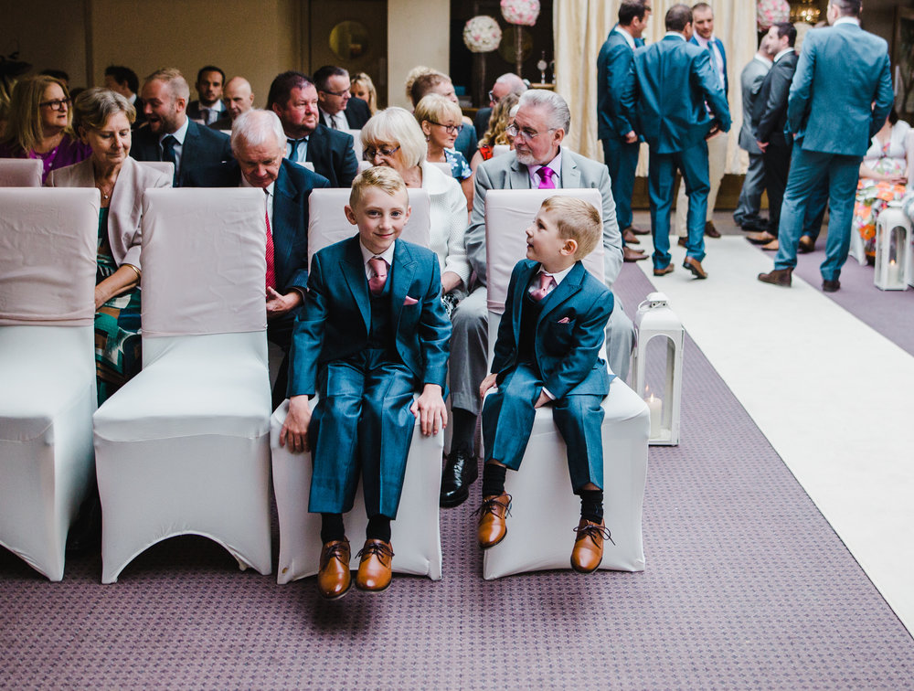 The little ones in their suits sat down- Documentary wedding photography