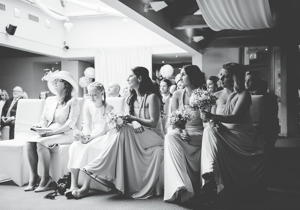 Black and white photograph of the wedding guests watching the bride and groom get wed at The White Hart Inn at Lydgate