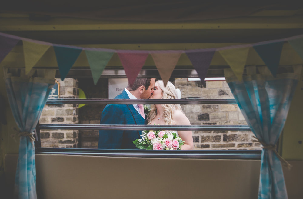 Creative photo of the bride and groom kissing through the camper van window - White Hart at Lydgate wedding